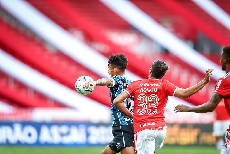 A bola está no alto e a frente de Ferreirinha, do Grêmio, enquanto Nonato, do Inter, empurra o gremista pelas costas dentro da área