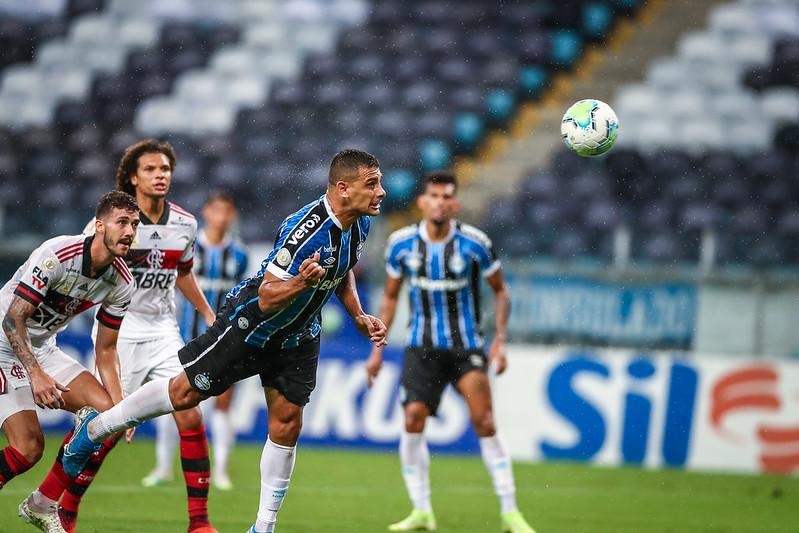 Diego Souza, atacante do Grêmio, cabeceia a bola em direção ao gol e dois zagueiros do Flamengo assistem ao lance que se transformou no primeiro gol da partida